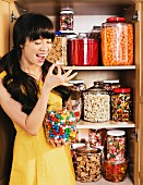 Mixed race woman eating candy from jar