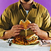 Overweight man eating hamburgers and french fries