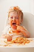 Crying, mixed race baby boy eating spaghetti