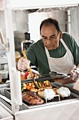 Hispanic man grilling meat in food cart