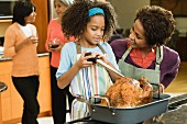 African American girl basting Thanksgiving turkey