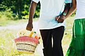 Afrikanisches Paar mit Picknickkorb auf einer Wiese