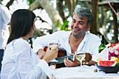 Südamerikanischer Mann spielt Gitarre für Frau beim Gartentisch