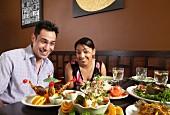 Paar an einem üppig gedeckten Tisch im Restaurant