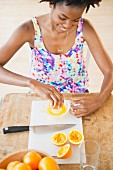 Black woman squeezing fresh orange juice
