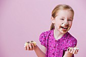 Messy girl holding birthday cake