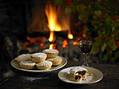 Mince pies and a glass of red wine in front of the fireplace