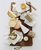 A still life featuring assorted cheeses on a wooden board (view from above)