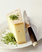 A slice of Raclette cheese on a plate with chives and a knife