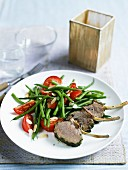 Lamb chops with a herb crust, green beans and tomatoes