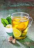 Ginger tea with limes in a glass cup