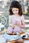 Mädchen schneidet ein Stück vom Brombeerkuchen ab