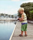 Kleiner Junge mit Angel auf einem Holzsteg