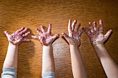 Cookie Sprinkles on Two Children's Hands, High Angle View