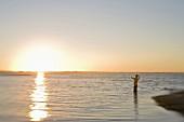 Mann beim Fliegenfischen bei Sonnenaufgang (Florida)