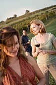 Friends Walking Through Vineyard with Wine