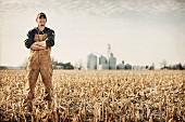 Bauer auf einem abgeernteten Maisfeld