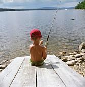 Kleiner Junge angelt am See