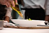 Chef adding olive oil to dish during service at working restaurant