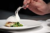 Koch garniert Fisch und Bohnen mit Schaumsauce in der Restaurantküche