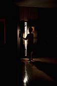 Junge in der dunklen Küche in den Kühlschrank schauend