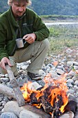 Man Starting Camp Fire and Drinking Coffee