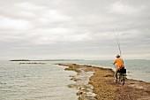 Angler auf einer Landzunge radelnd