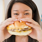 Close up of mixed race teenage girl eating cheeseburger