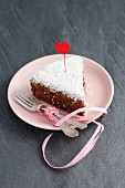 A slice of chocolate cake with grated coconut and a heart decoration