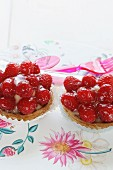 Two strawberry tartlets on a floral tablecloth with plastic cutlery in the background