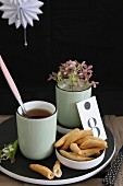 Savoury snacks, mug of tea and stem of flowers on black wooden board against dark background