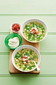 Pea and potato soup with sour cream and diced bacon