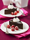 Two slices of chocolate espresso cake with raspberries and cream