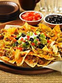 Nachos with cheese sauce, olives, tomatoes, coriander and sour cream (Mexico)