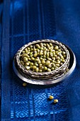Mung beans on a blue silk sari in a stack of Indian bangles