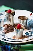 pots of chocolate and raspberry mousse on a vintage plate
