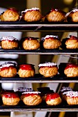 Choux buns with red caramel topping and sugar crystals on shelves in a bakery