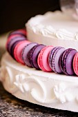 Purple and pink macaroons on a white cream layer cake