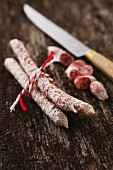 Mini salami on a wooden surface with a knife