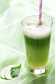 Grüner Vitaminsaft im Glas mit Strohhalm