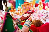 Inderin in traditioneller Kleidung hält Reis in bemalten Händen
