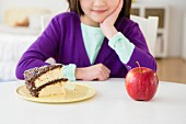 A girl sitting at a table in front of a slice of cake and an apple