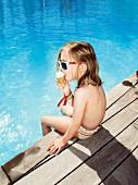 Kleines Mädchen mit Eis an einem Pool sitzend