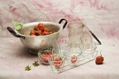 Strawberries in a colander and in glass bowls