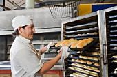 Bäcker mit fertiggebackenen Broten auf Backblech