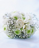 A white wedding bouquet with baby's breath, roses and gerberas