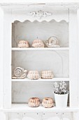 Mini Bundt cakes with icing sugar on a vintage kitchen shelf