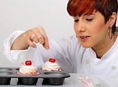 Frau beim Dekorieren von Cup Cakes