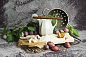 Plums, flour, yeast and kitchen utensils