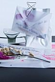 Mit Sesamkörnern und Blütenblättern gefüllter Briefumschlag aus Transparentpapier, mit Büroklammer an Tütenvase angeklemmt
